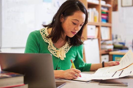Female teacher grading papers