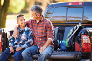 Father and son talking while sitting on the tailgate of a truck