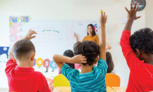 Kids in a class room raising their hands