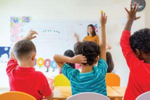 Kids in a class romm raising their hands