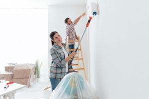 Couple painting a room in their house