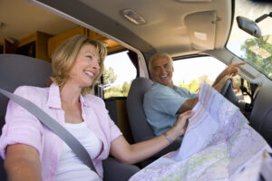 mature woman with map in motor home, next to husband, smiling, low angle view.