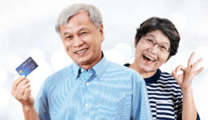 """Mature Asian couple in front of white background. Man holding credit card. Woman making """"OK"""" symbol with fingers."""