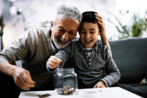 grandfather and grandson smiling, sitting on couch, counting lose change into a jar.